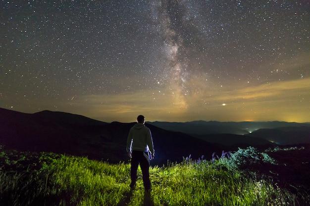 Dunkles schattenbild eines mannes, der in den bergen nachts milchstraßeansicht genießend steht. Premium Fotos