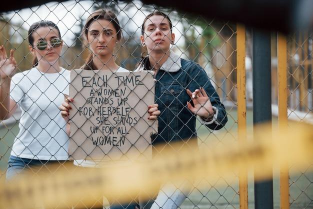 Durch den zaun. eine gruppe feministischer frauen protestiert im freien für ihre rechte Kostenlose Fotos