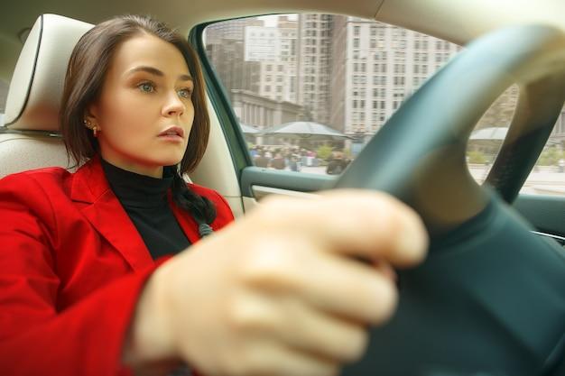 Durch die stadt fahren. junge attraktive frau, die ein auto fährt. junges hübsches kaukasisches modell in der eleganten stilvollen roten jacke, die am modernen fahrzeuginnenraum sitzt Kostenlose Fotos