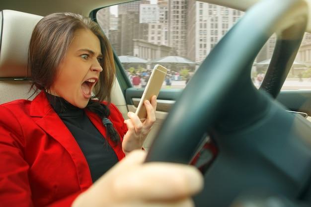 Durch die stadt fahren. junge attraktive frau, die ein auto fährt Kostenlose Fotos
