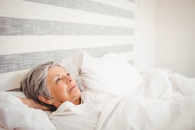 Durchdachte ältere frau, die auf bett sich entspannt Premium Fotos