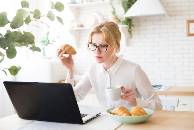 Durchdachte geschäftsfrau, die laptop beim essen des hörnchens verwendet Kostenlose Fotos