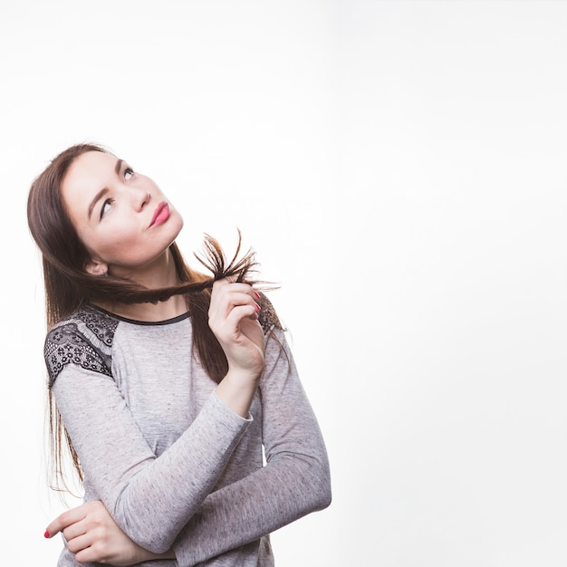 Durchdachte junge frau, die ihr brunettehaar wirbelt Kostenlose Fotos
