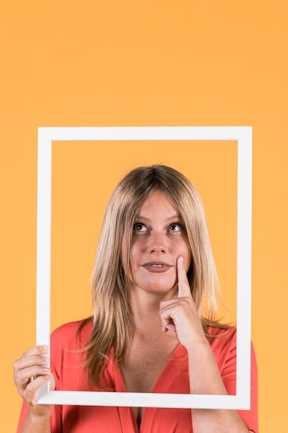 Durchdachte taube frau, die rahmenausschnitt auf gelbem hintergrund hält Kostenlose Fotos