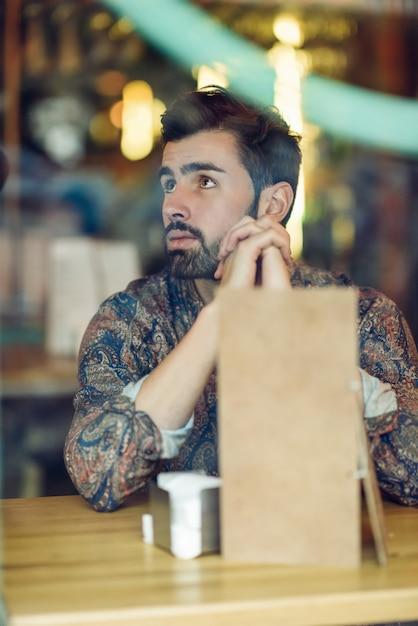 Durchdachter bärtiger mann, der die zufällige kleidung sitzt in einer modernen kneipe trägt. Premium Fotos