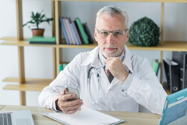 Durchdachter doktor mit smartphone Kostenlose Fotos