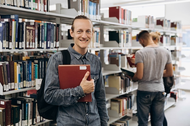 Durchdachter junge sieht wie ein student aus, der mit buch in der bibliothek einer universität steht Premium Fotos