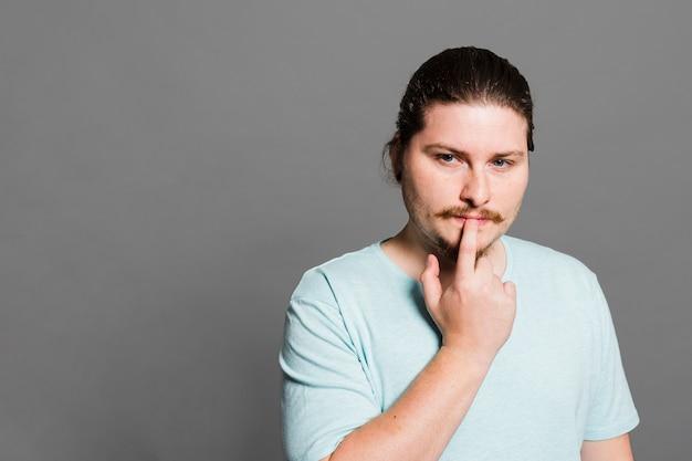 Durchdachter junger mann mit seiner hand auf lippen gegen grauen hintergrund Kostenlose Fotos