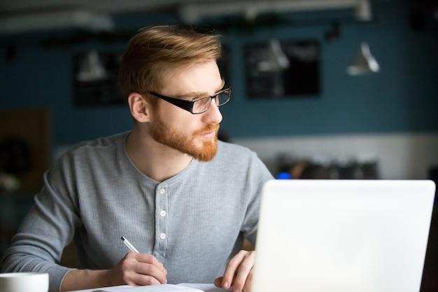 Durchdachter mann, der an anmerkungen des neuen ideenschreibens im café denkt Kostenlose Fotos