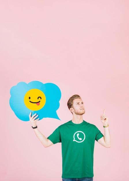 Durchdachter mann, der aufwärts beim anhalten des blinzelns der emoji spracheblase zeigt Kostenlose Fotos