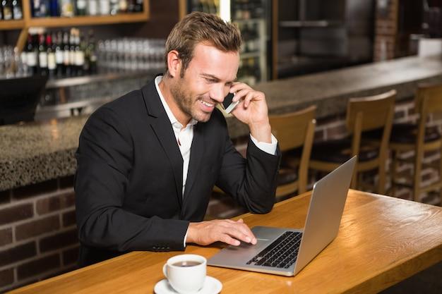 Durchdachter mann, der laptop verwendet und einen telefonanruf hat Premium Fotos