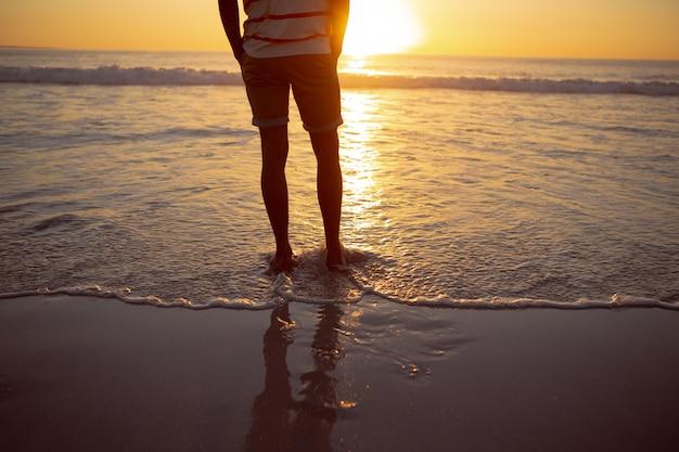Durchdachter mann, der mit den händen in der tasche auf dem strand steht Kostenlose Fotos