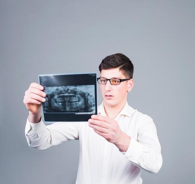 Durchdachter mann, der zahnröntgenstrahl betrachtet Kostenlose Fotos