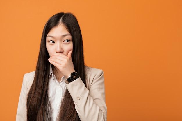 Durchdachtes schauen der jungen geschäftsfrau zu einem kopienraum-bedeckungsmund mit der hand. Premium Fotos
