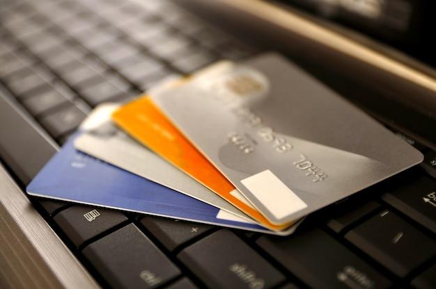 E-commerce-konzept. gruppe von kreditkarten und laptop mit flachem dof Premium Fotos