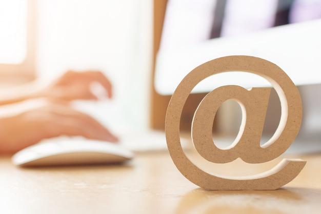 E-mail-marketing-konzept, hand unter verwendung des computers, der mitteilung mit hölzernem e-mail-adressensymbol sendet Premium Fotos