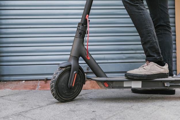E-roller-mitfahrer der ansicht von unten, der eine pause macht Kostenlose Fotos