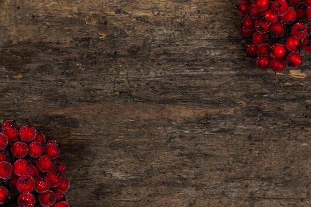 Ebereschenbeeren auf rustikalem hölzernem hintergrund mit kopienraum. herbsthintergrund mit roten beeren. weihnachtshintergrund mit roten beeren Premium Fotos