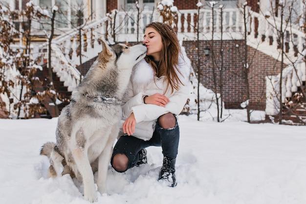 Echte freundschaft, schöne glückliche momente der bezaubernden jungen frau mit dem niedlichen husly-hund, der kalte winterzeit auf der straße voll mit schnee genießt. beste freunde, tierliebe, wahre gefühle, einen kuss gegeben. Kostenlose Fotos