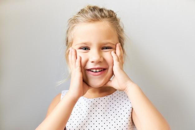 Echte menschliche reaktionen und gefühle. porträt des schönen niedlichen kleinen jungen im gepunkteten kleid, das hände auf ihren pummeligen wangen hält, überglücklichen glücklichen gesichtsausdruck, aufgeregt mit geburtstagsgeschenk Kostenlose Fotos