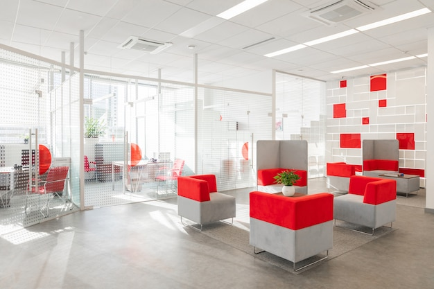 Ecke des modernen büros mit weißen wänden, grauem boden, offenem raumbereich mit den roten und weißen lehnsesseln und räumen hinter glaswand Premium Fotos