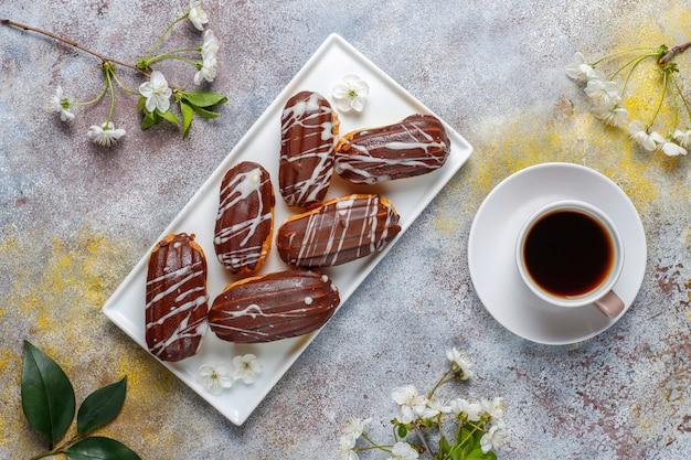 Eclairs oder kränzchen mit schwarzer schokolade und weißer schokolade mit pudding im inneren, traditionelles französisches dessert. Kostenlose Fotos