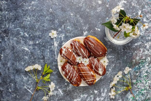 Eclairs oder kränzchen mit schwarzer schokolade und weißer schokolade mit pudding im inneren Kostenlose Fotos