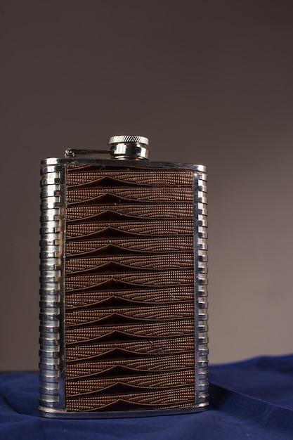 Edelstahl-flachmann lokalisiert auf einem grauen hintergrund Premium Fotos