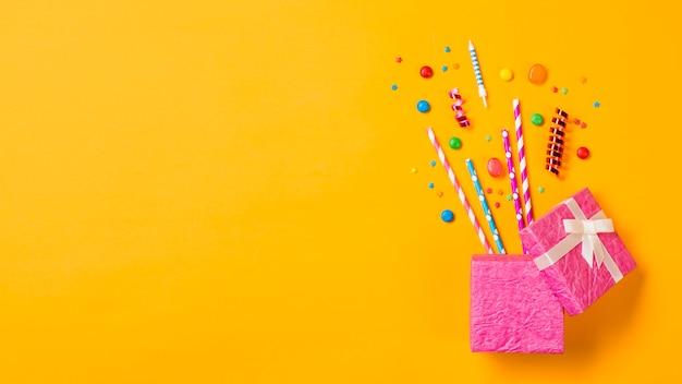 Edelsteine; strohhälme; luftschlangen; streusel aus dem offenen rosa kasten auf gelbem hintergrund Kostenlose Fotos