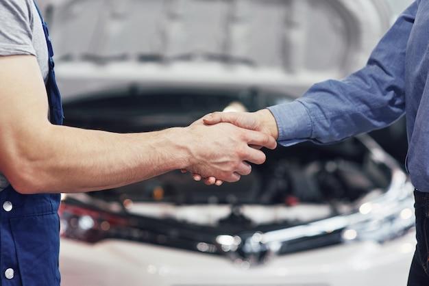Ehemann automechaniker und kundin vereinbaren die reparatur des autos Kostenlose Fotos