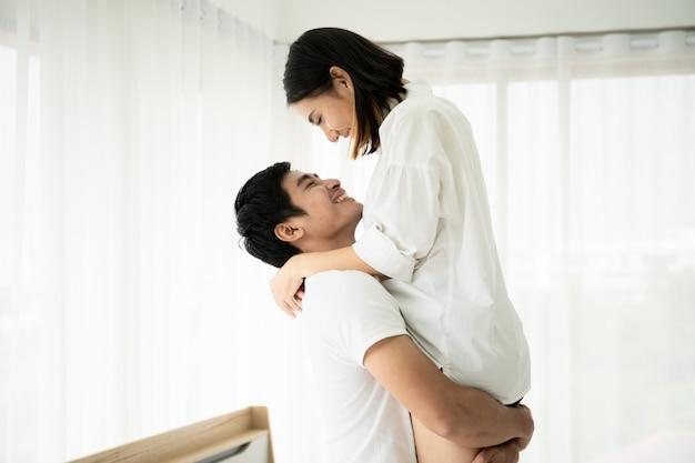 Ehemann, der seine frau hochhält und im schlafzimmer, im paar und in der beziehung küsst. paar in valentinstag. Premium Fotos