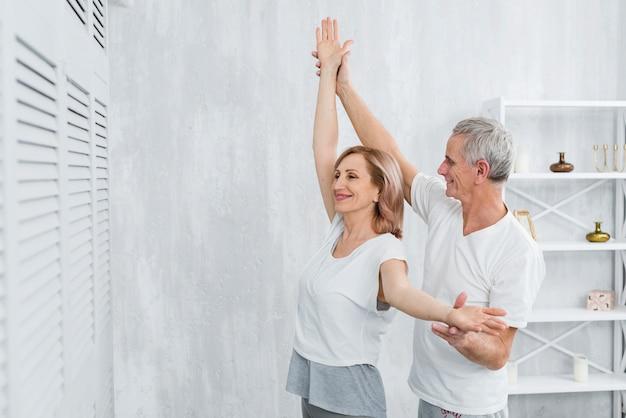 Ehemann, der seine frau unterstützt, wenn er yogaübung tut Kostenlose Fotos