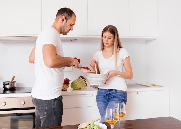 Ehemann, der seiner frau beim kochen von essen in der küche hilft Kostenlose Fotos