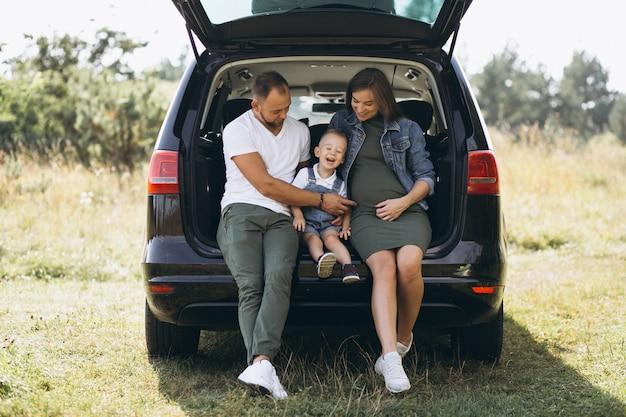 Ehemann mit der schwangeren frau und ihrem sohn, die im auto sitzen Kostenlose Fotos