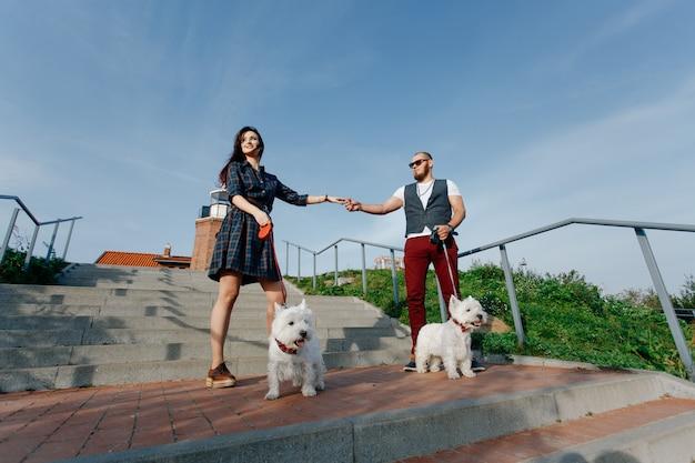Ehemann mit einer schönen frau, die ihre weißen hunde in der straße geht Premium Fotos