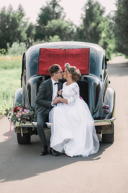 Ehemann und frau des liebevollen paares sitzen im stamm eines retro- autos, das an ihrem hochzeitstag küsst. Premium Fotos
