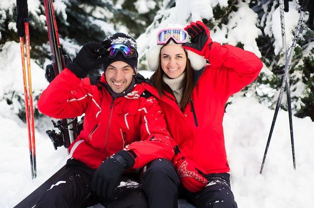 Ehepaar in hellen jacken, die sich darauf vorbereiten, gemeinsam im winterwald ski zu fahren. Premium Fotos