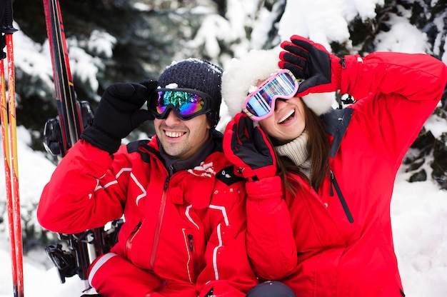 Ehepaar in hellen jacken, die sich darauf vorbereiten, gemeinsam im winterwald ski zu fahren Premium Fotos