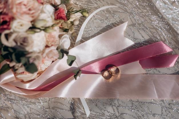 Eheringe auf den gedämpften rosa bändern und dem zarten hochzeitsblumenstrauß Kostenlose Fotos