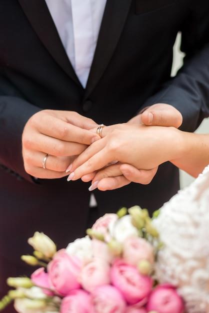 Eheringe und hände von braut und bräutigam. junges hochzeitspaar bei der zeremonie. ehe. mann und frau verliebt. zwei glückliche menschen, die feiern, familie zu werden Premium Fotos