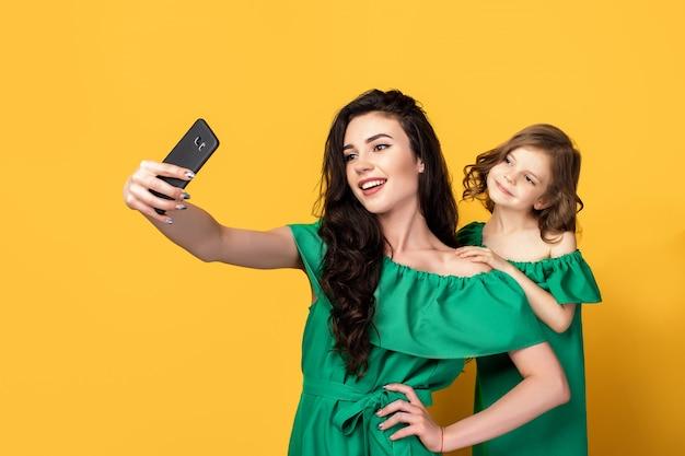 Ehrfürchtige mutter mit der tochter, die selfie nimmt Premium Fotos