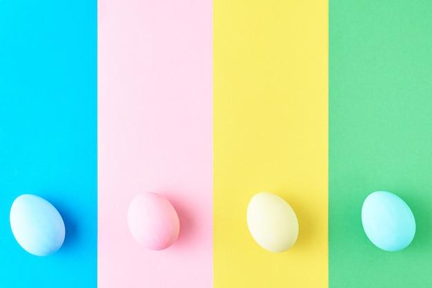 Eier auf farbigem gestreiftem hintergrund, draufsicht, minimalismuskonzept Premium Fotos