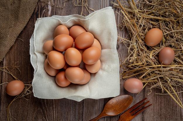 Eier in tassen auf sackleinen mit trockenem gras. Kostenlose Fotos