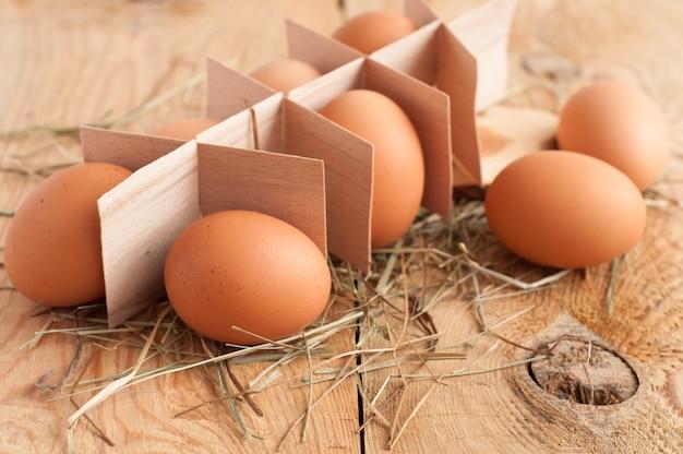 Eier und heu auf hölzernem hintergrund Premium Fotos