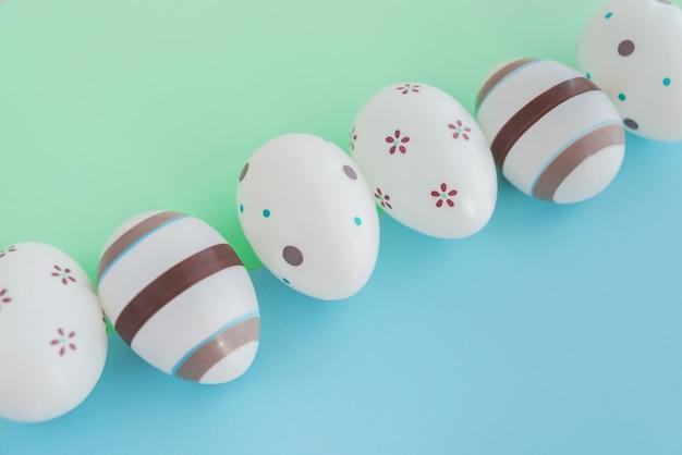 Eier verziert mit streifen und blumen auf grünem und blauem hintergrund, ostern-konzept. Premium Fotos