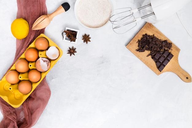 Eierkarton; mehl; zitrone; sternanis; schokoriegel und hölzerne saftpresse auf weißem hintergrund Kostenlose Fotos