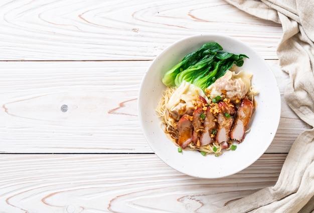 Eiernudel mit rotem gebratenem schweinefleisch und wonton Premium Fotos