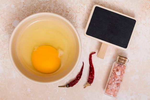 Eigelb und eiprotein in einer schüssel mit chilischoten; himalayasalz und leeres plakat Kostenlose Fotos