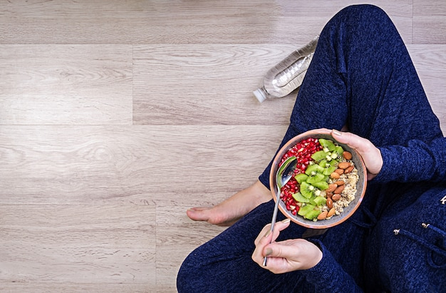 Eignung und gesundes lebensstilkonzept. frau ruht sich aus und isst ein gesundes hafermehl nach einem training. ansicht von oben. Kostenlose Fotos