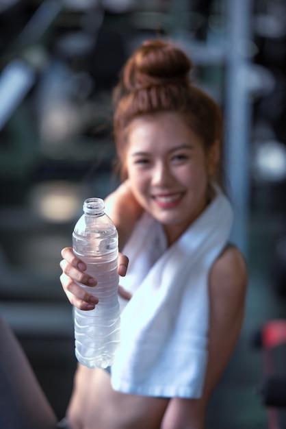 Eignungs-frau mit trinkwasser in der turnhalle. Premium Fotos